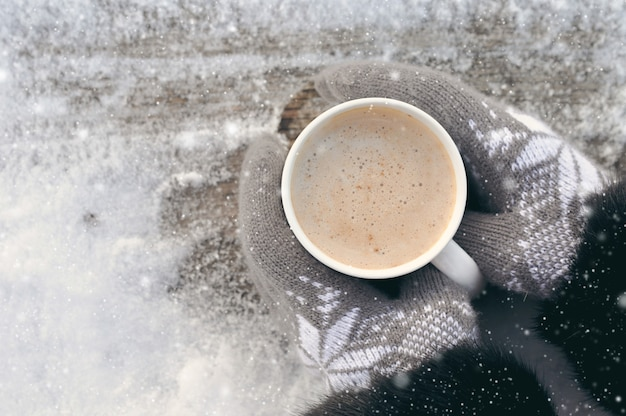 Winter picture: hands in knitted gray gloves holding a cup of hot coffee on a snowy day on a wooden rustic background in the village. copyspace. top view