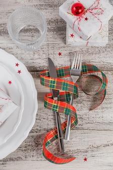 Урегулирование места зимы с украшениями рождества и нового года на белом деревянном столе. сервировка праздничного стола для рождественского ужина. плоская планировка