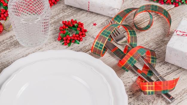 Урегулирование места зимы с украшениями рождества и нового года на белом деревянном столе. сервировка праздничного стола для рождественского ужина.