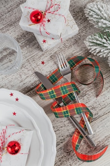 Winter place setting with christmas and new year decorations on white wooden table. festive table setting for christmas dinner. top view