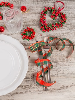 Winter place setting with christmas and new year decorations on white wooden table. festive table setting for christmas dinner.