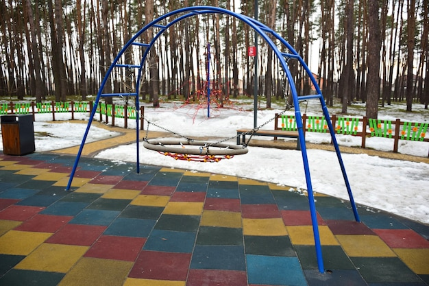 On a winter playground in the forest, an empty decorative hanging swing without children