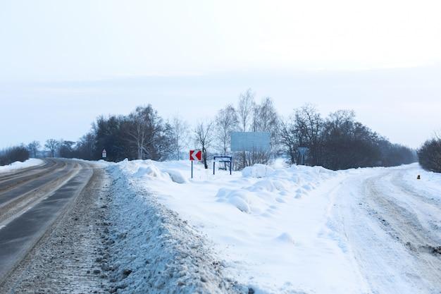 冬は道路の清掃が不十分です。雪が散らばって田舎の道。吹きだまり