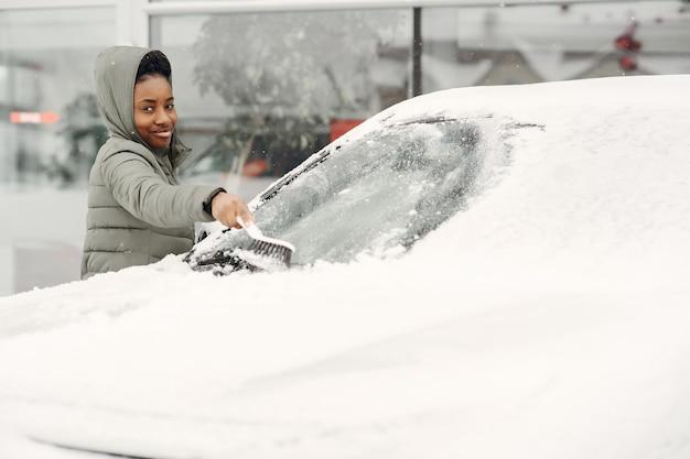 Ritratto di inverno della donna africana che pulisce la neve da un'auto. donna in una giacca verde.