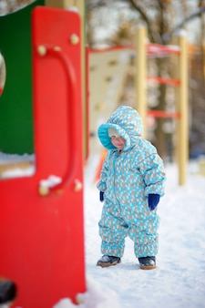 Winter portrait of beautiful toddler boy on playground