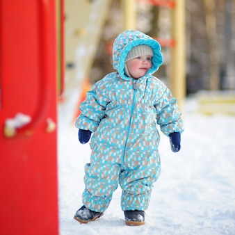 Winter portrait of beautiful toddler boy on snow