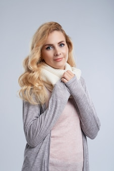 Winter portrait of caucasian woman wrapping up in warm wool scarf