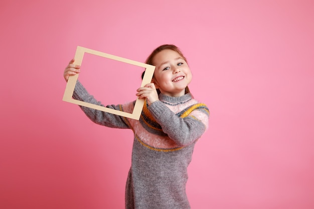 Winter portrait of a little smiling girl holding blank frame for mock-up on a pink background