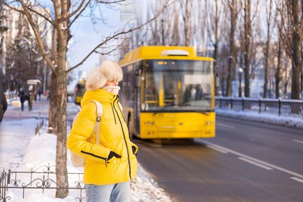 雪に覆われた街の通りでバスを待っている暖かい黄色のジャケットとシベリアロシアの帽子で幸せな女性の冬の肖像画