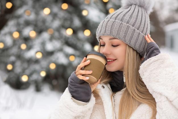 Зимний портрет радостной молодой женщины в теплой одежде держит чашку горячего кофе. пустое пространство