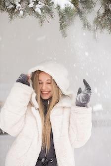 森で雪と遊ぶ笑う若い女性の冬の肖像画