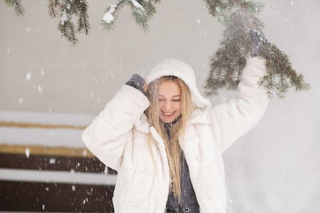 森で雪と遊ぶ感情的な若い女性の冬の肖像画。空きスペース