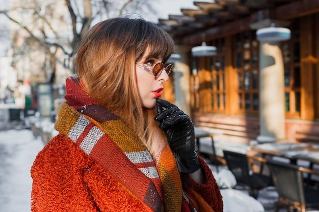 屋外ポーズレトロなメガネでエレガントなブルネットの女性の冬のポートレート