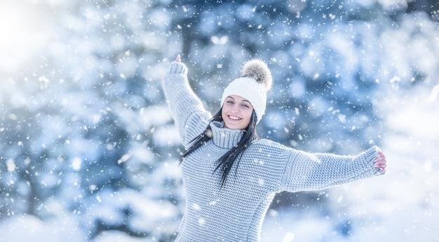 Зимний портрет счастливой привлекательной молодой женщины в теплой одежде