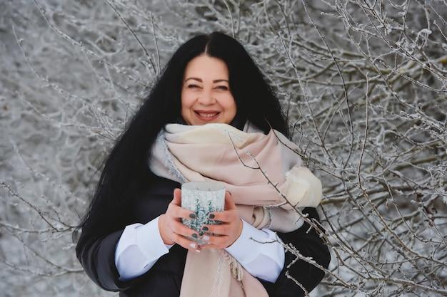雪の森で笑顔の若いブルネットの女性の冬の肖像画。