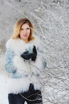 雪の森で笑顔の若い女性の冬の肖像画。