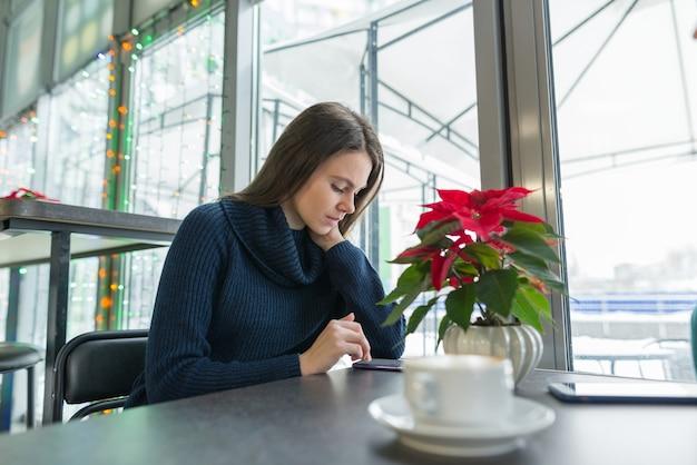 Зимний портрет женщины, сидя в кафе с чашкой кофе