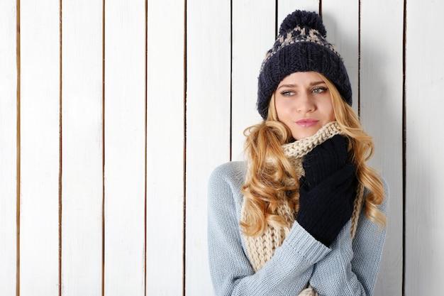 彼女のニットの暖かい服を着た若い美しいブロンドの女性の冬の肖像画