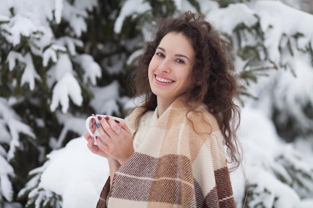 눈에 덮여 니트 목줄을 입고 젊은 아름 다운 갈색 머리 여자의 겨울 초상화