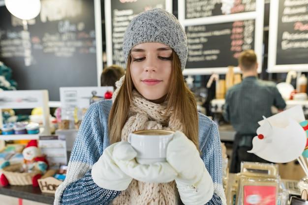 Зимний портрет молодой красивой женщины с чашкой кофе.