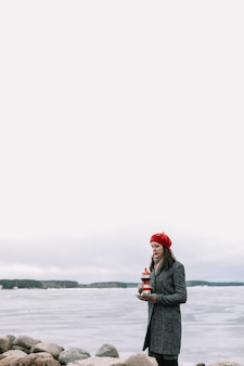 Зимний портрет молодой женщины в пальто и красной шляпе, держащей декоративный маяк и стоящей на берегу замерзшего моря. зима, путешествия, морской фон. ветреная погода, изумительное ледяное побережье