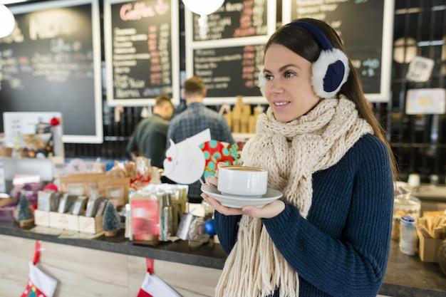 Зимний портрет молодой женщины в вязаном свитере с чашкой