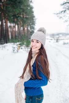 Winter portrait of young beautiful brunette woman wearing knitted snood covered in snow. woman in winter forest