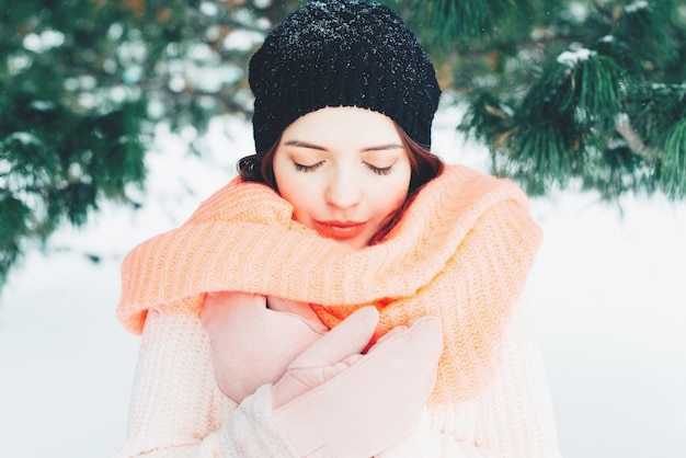 Winter portrait of young brunette woman wearing pink knitted snood. girl with eyes closed.
