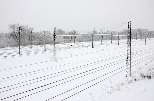 Winter railway landscape, railway tracks in the snow-covered industrial country
