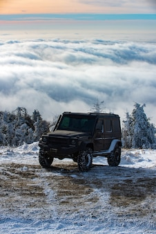 4x4 자동차가 있는 겨울 여행 컨셉입니다. 오프로드 겨울 자동차. 모험 여행. 눈 산 도로에서 오프로드 여행.