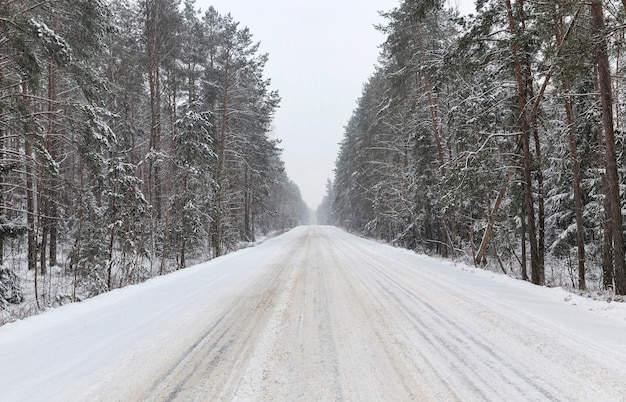 降雪後雪に覆われた冬の車を運転するための冬の道