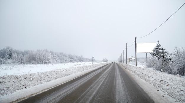 Зимняя дорога с рекламным баннерным щитом за городом
