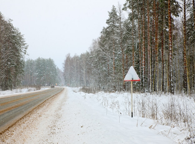Winter road with a dangerous turn with warning sign