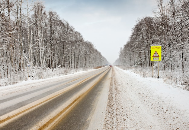 Winter road with warning sign