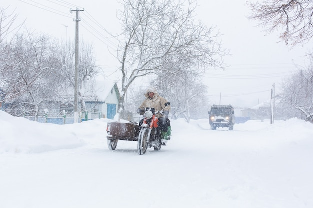 Winter, rural streets are covered with snow, a man rides a motorcycle in a snowstorm.