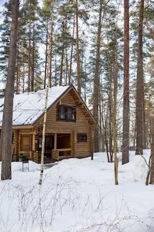 冬の物語。美しい雪の森のフィンランドのコテージ。冬の松林の木製のカントリーハウスのコテージ、屋根は雪で覆われています。別荘。北の自然