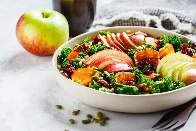 Winter salad with apple, pumpkin, cranberries, honey and seeds in white plate.