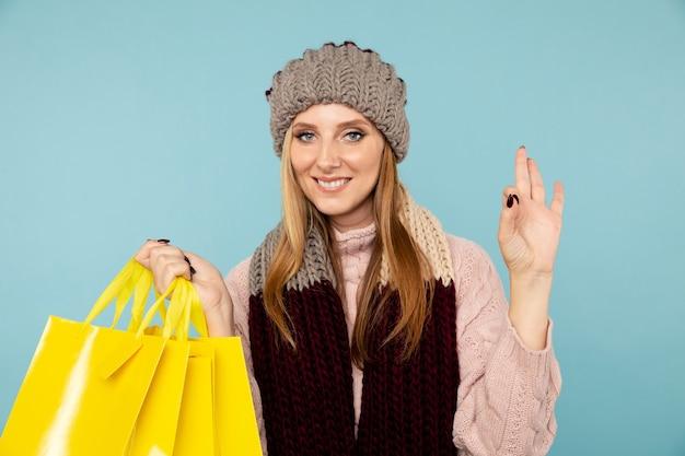 겨울 세일. 가방을 들고 모자에 젊은 웃는 여자.