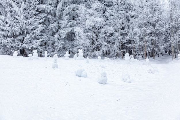 Winter scene in a rest zone near a forest. benches and snowmen, forest road