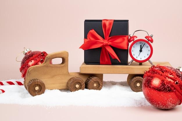 Зимняя сцена с деревянной рождественской тележкой и подарочной коробкой. фото высокого качества