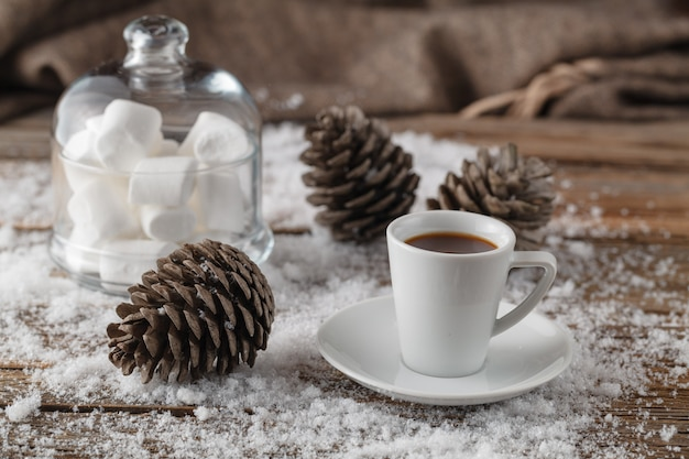 Winter scene of wooden old table with  snow and mug