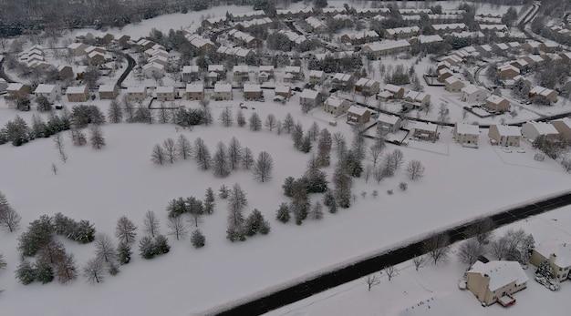 冬の風景の屋根は、空撮の降雪後の冬の日に雪に覆われた住宅の小さな町を収容します