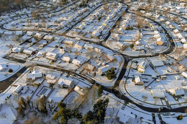 冬の風景の屋根は、空撮の降雪後の冬の日の間に雪に覆われた住宅の小さな町を収容します