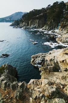 Зимний морской пейзаж, скалы на море со льдом, горы.