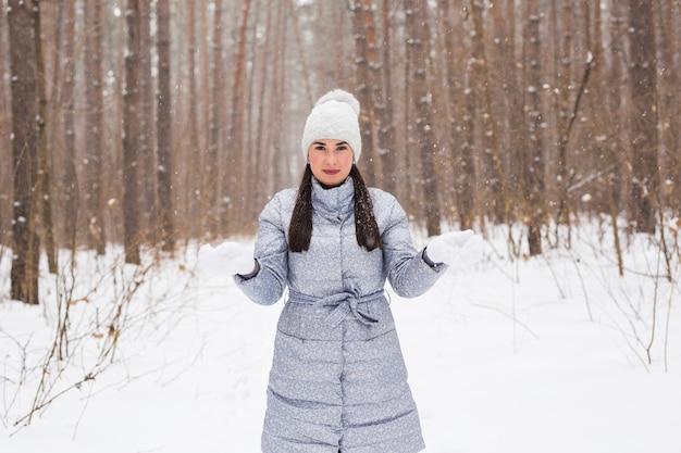 冬、季節、人々の概念-冬の公園を歩く灰色のコートと白い帽子の女性と
