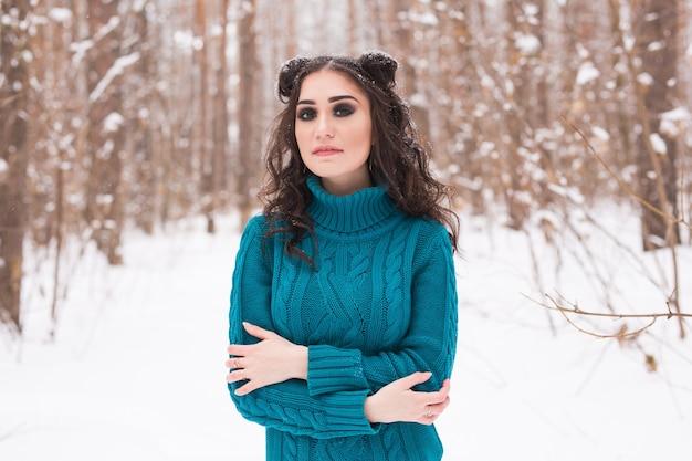 冬、季節、人々の概念-雪の公園を歩く若いきれいな女性