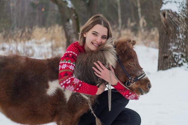 冬の美しい少女とポニー馬