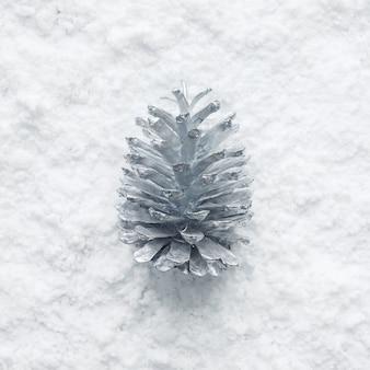 冬の季節、シルバーの松ぼっくりと雪のクリスマスコンセプトのアイデア