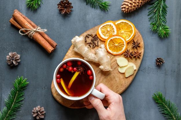 冬のシーズンのコンセプトです。レモン、クランベリー、クローブ、アニス、生姜と熱いお茶のカップを持っている男性の手のフラットレイアウト。風邪のための自然療法。