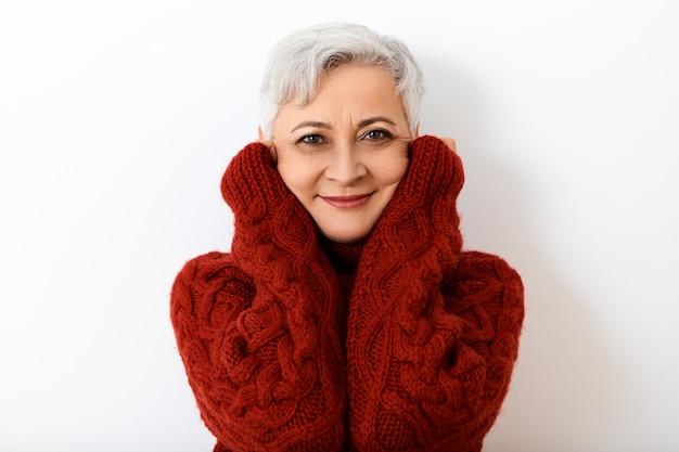 Inverno, stagione, intimità, stile e concetto di abbigliamento. colpo isolato del pensionato femminile caucasico elegante affascinante con capelli grigi corti che posano al muro bianco, avvolto in un maglione lavorato a maglia caldo
